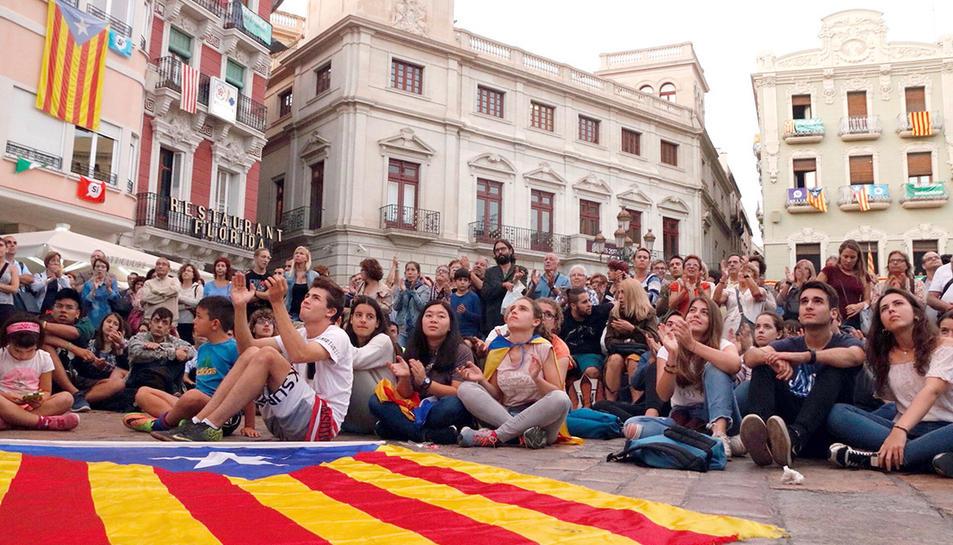 Una estelada estirada a terra davant dels ciutadans que segueixen des de la plaça del Mercadal de Reus la compareixença del president Carles Puigdemont.