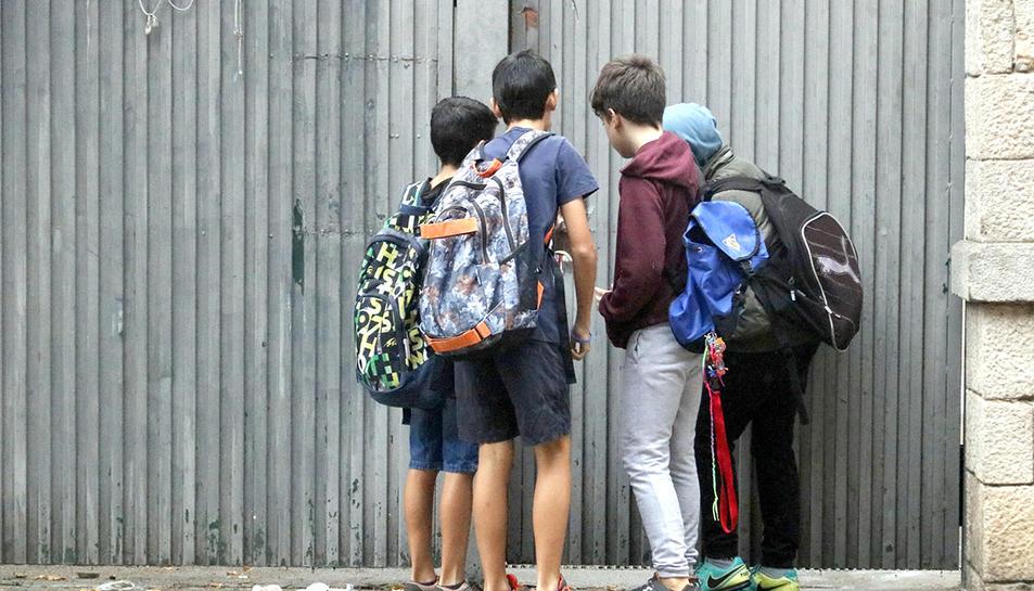 Un grup d'alumnes del col·legi Verd de Girona, comprovant els desperfectes a la porta d'entrada.
