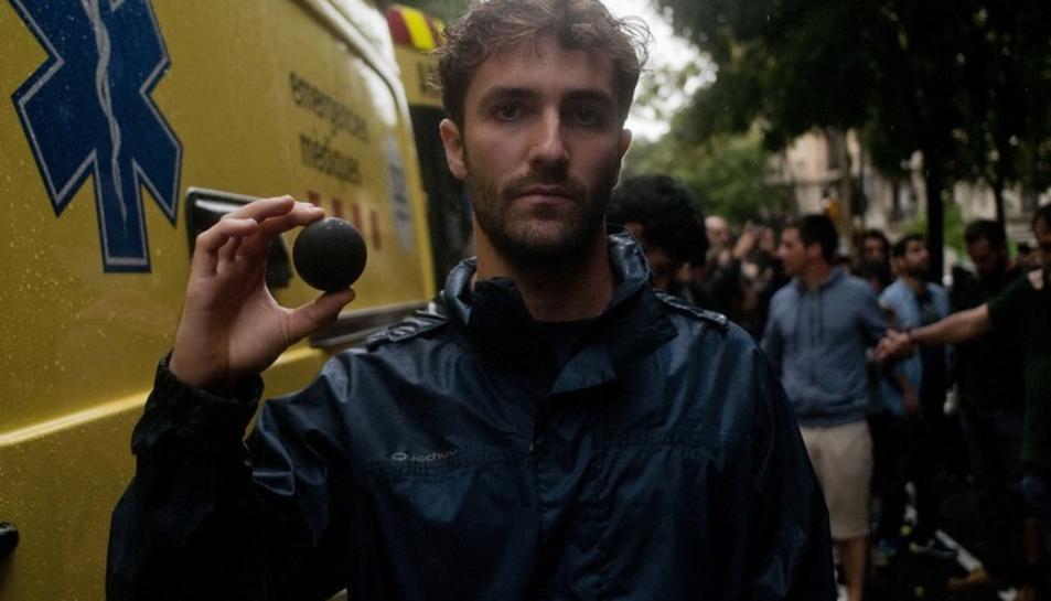 Un jove mostra una pilota de goma després d'una càrrega policial a BArcelona.