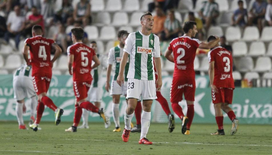 Markovic, del Córdoba, es lamenta per la golejada. Al fons de la imatge, jugadors del Nàstic celebrant un dels gols anotats diumenge.