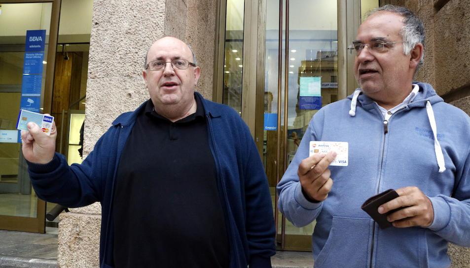 Ramon Pàmies i Joan Moncusí mostrant les seves targetes de crèdit després de retirar 150 euros en un caixer del BBVA de la plaça Prim de Reus.