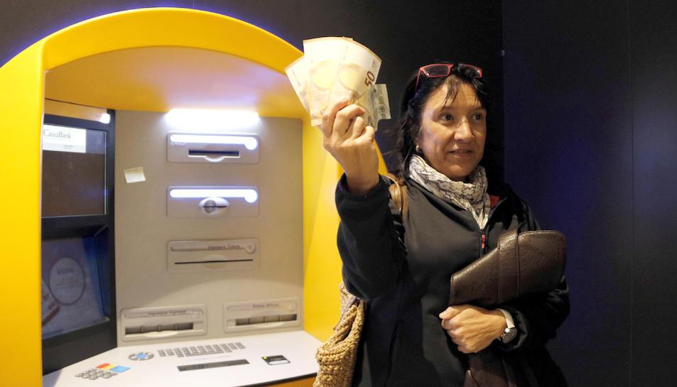 Una dona mostrant els diners que ha tret del caixer seguint la proposta de la Crida per la Democràcia.