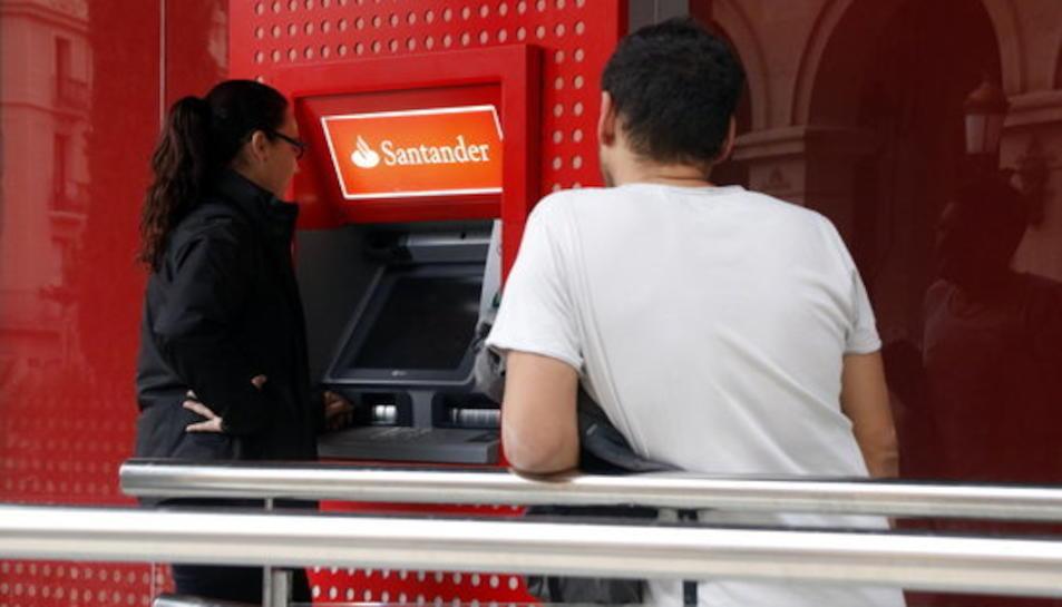 Pla mig de dues persones fent cua al caixer del Santander, a la plaça Prim de Reus, el 20 d'octubre del 2017.