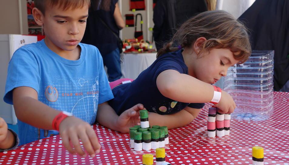 Pla mig de dos nens jugant a apilar taps com si siguin castells, durant la Fira Castells. Imatge del 21 d'octubre de 2017