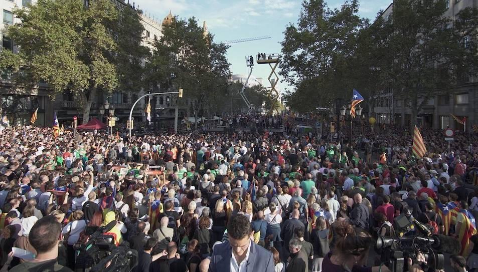 Milers de persones omplint el Passeig de Gràcia davant l'escenari de la manifestació.
