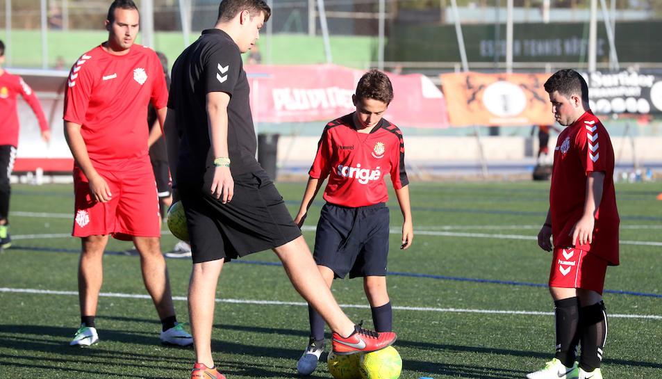 A la imatge, en Carlos Rovira ajuda als jugadors del Nàstic Genuine en allò que necessiten. Els entrenaments es realitzen tots els dilluns a l'annex de gespa artificial del Nou Estadi.