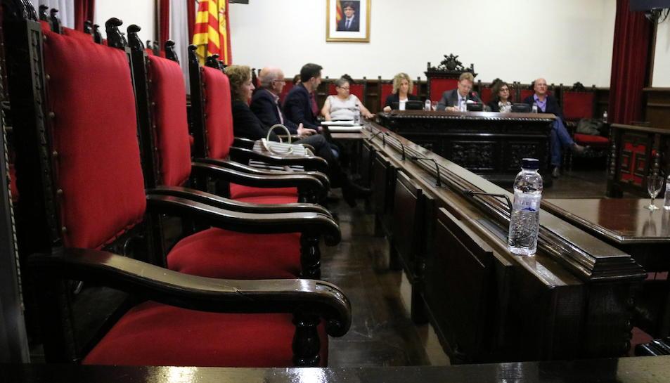Primer pla de les cadires buides dels regidors del PSC al ple de Tortosa i al fons la paret on ha desaparegut la foto del rei Felip VI.