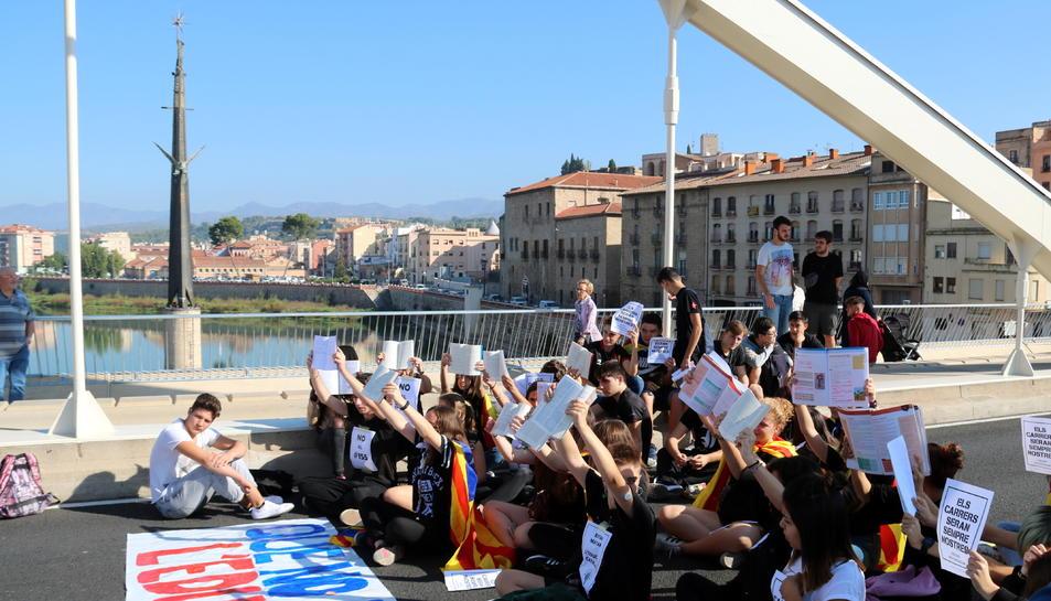 Els estudiants asseguts al pont de l'Estat de Tortosa aixecant llibres en català davant del monument franquista de l'Ebre.