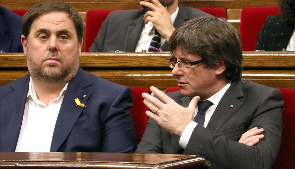 El president de la Generalitat, Carles Puigdemont, parla amb el vicepresident, Oriol Junqueras, al Parlament