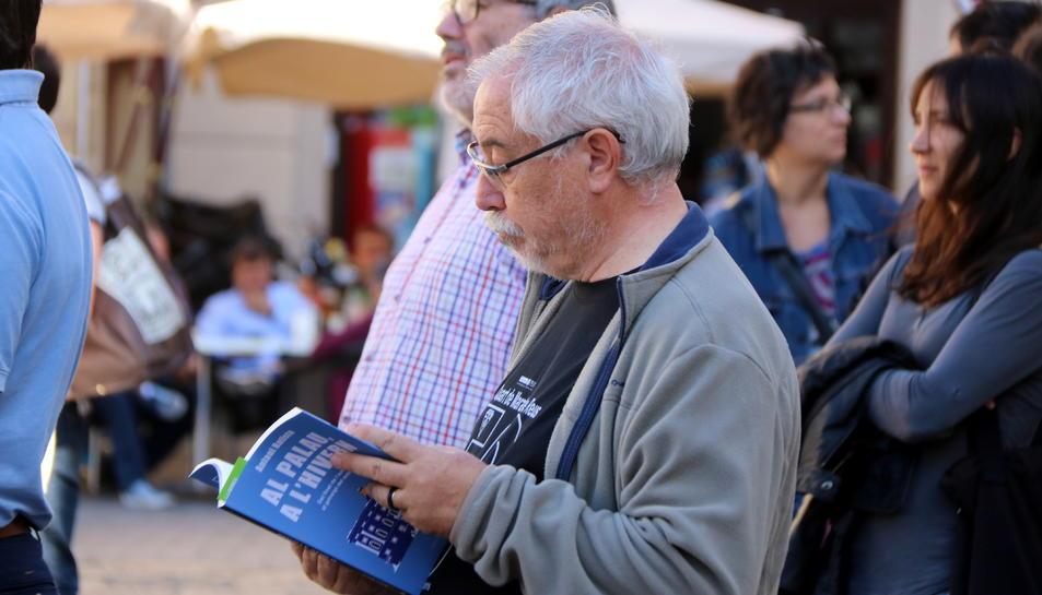L'exalcalde socialista de Reus, Lluís Miquel Pérez, llegint el llibre 'Al Palau, a l'hivern', d'Antoni Batista, a la plaça del Mercadal mentre intervenia la portaveu del PSC, Eva Granados.
