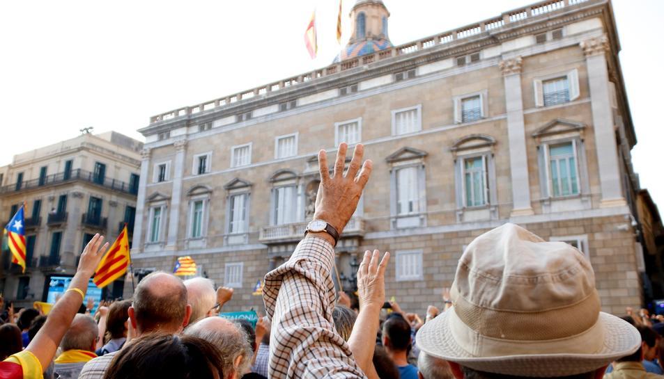 Un home aixecant els quatre dits davant la façana del Palau de la Generalitat.