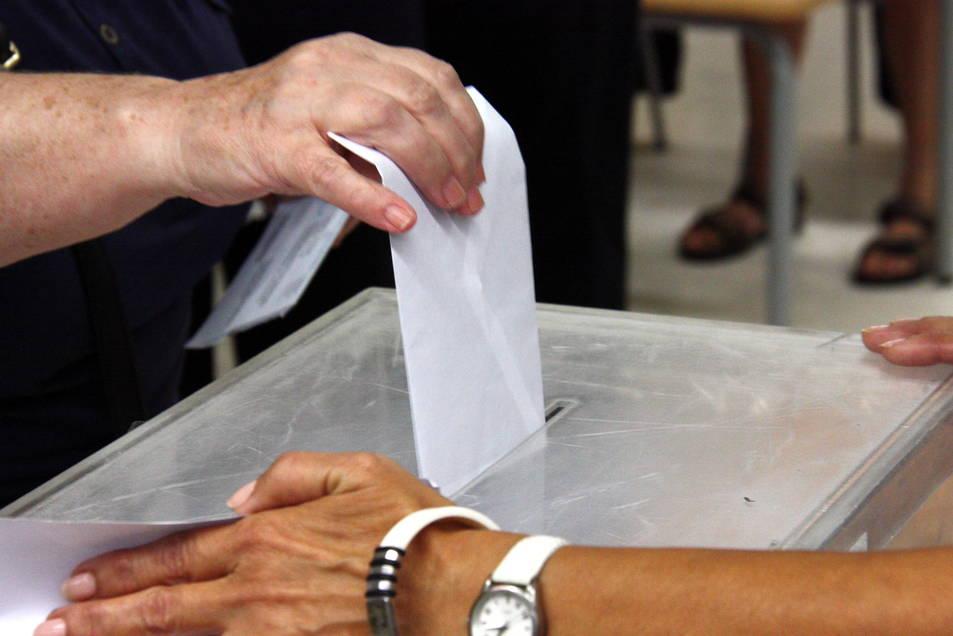Detall d'un votant introduïnt la papereta en una urna
