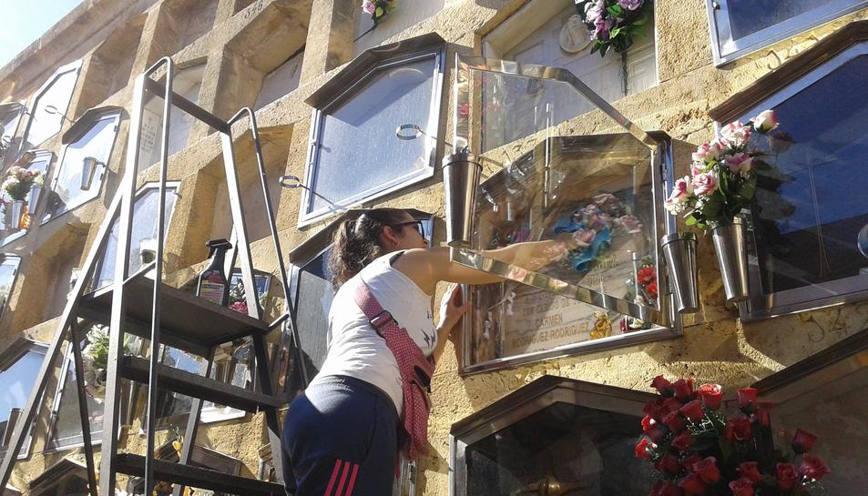 Sonia Plou neteja i posa flors al sarcòfag on descansen membres de la seva família.