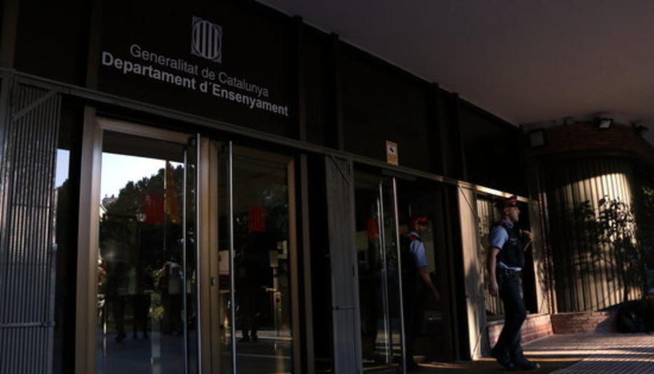Pla sencer de dos agents dels mossos d'esquadra sortint del Departament d'Ensenyament a quarts de 9 del matí del 30 d'octubre de 2017.