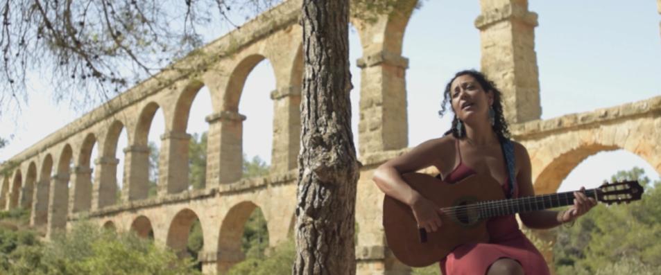 Imatge d'una escena del videoclip Olvidar, de Sara Veneros, amb el Pont del Diable de fons.
