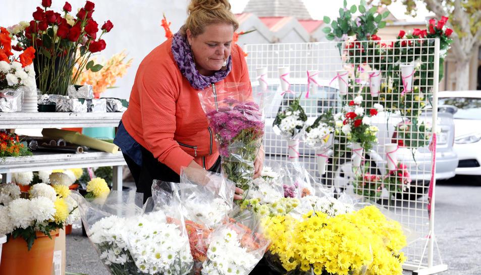 Diverses persones venen flors durant Tots Sants.