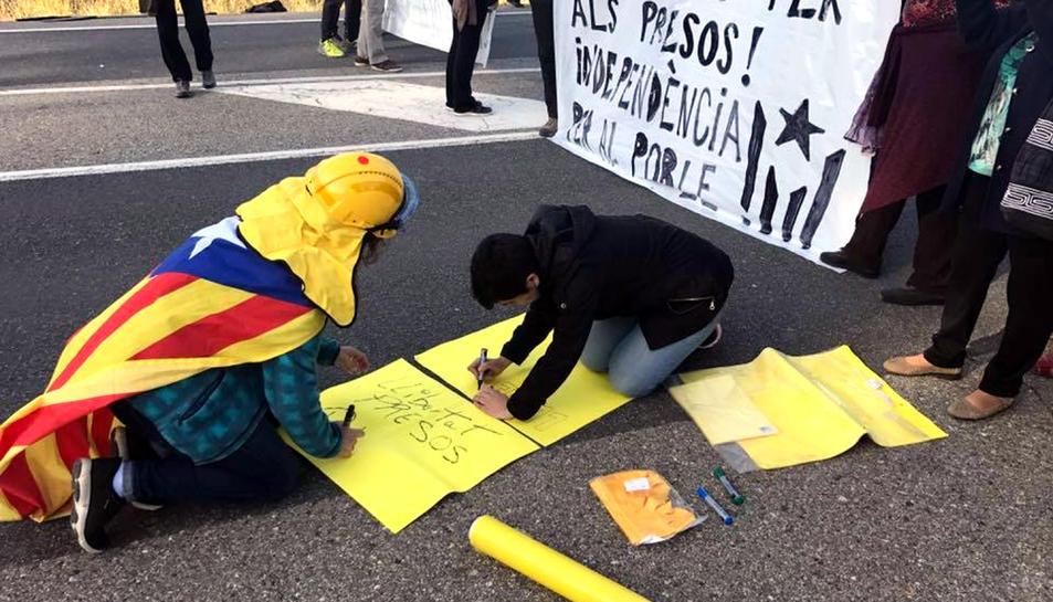 Alguns veïns pintant cartells i sostenint pancartes en el tall de trànsit que s'ha fet a la carretera T-333 entre Arnes.