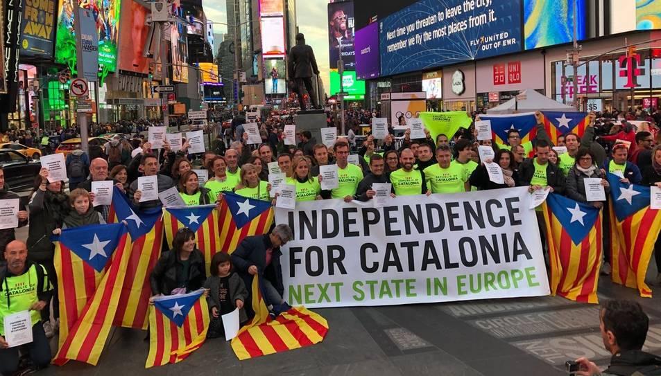 Fotografia de diversos corredors de la Marató de Nova York a Times Square amb estelades i pancartes demanant l'alliberament dels presos polítics.