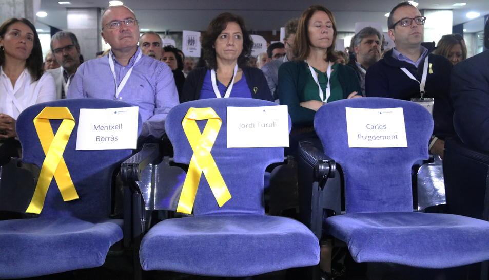 Cadires buides i llaços grocs en record als consellers del PDeCAT empresonats, i per al president Carles Puigdemont, en l'inici del Consell Nacional del PDECAT.