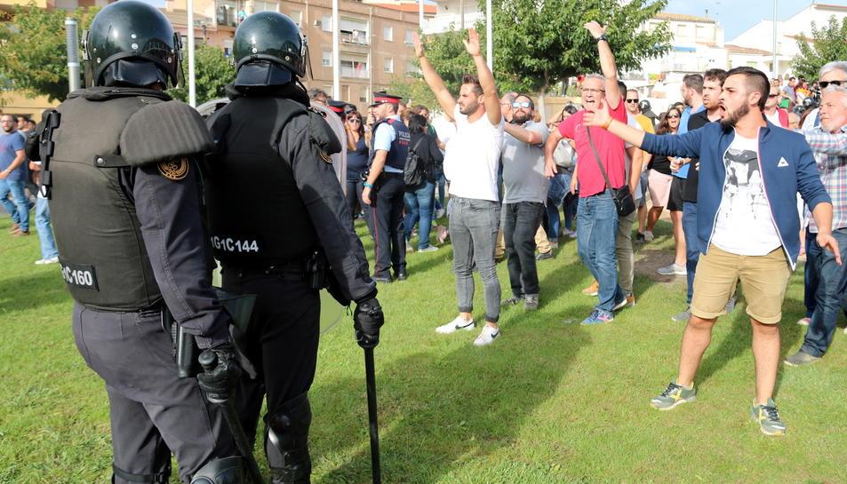Dos agents antiavalot de la Guàrdia Civil davant de diversos ciutadans amb els braços enlaire després d'entrar al Pavelló Firal de Móra la Nova i endur-se una urna.