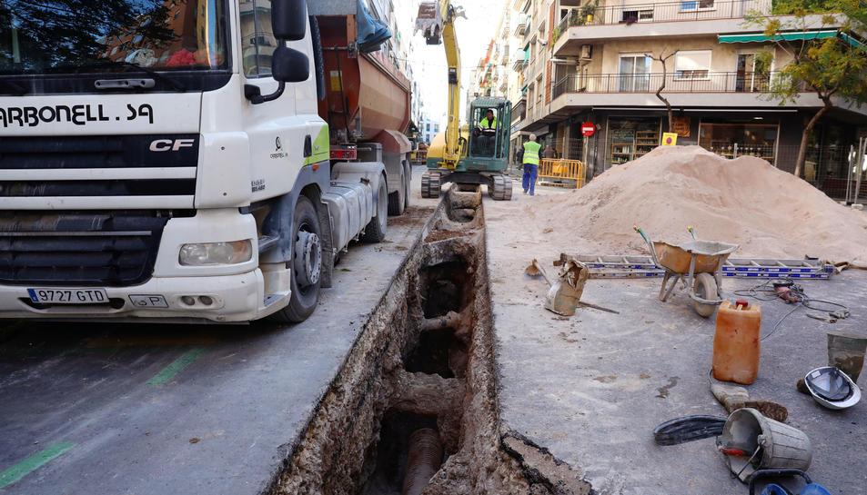 Un camió i una excavadora treballen al lloc on s'ha fet una rasa per canviar les canonades.