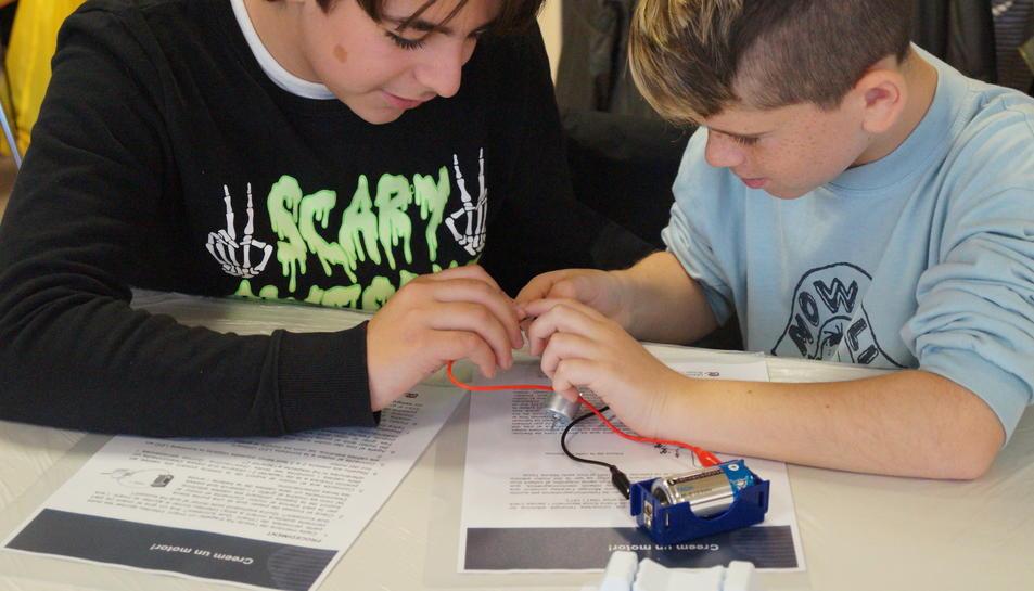 Uns alumnes intentant generar electricitat a partir de la construcció d'un motor senzill.