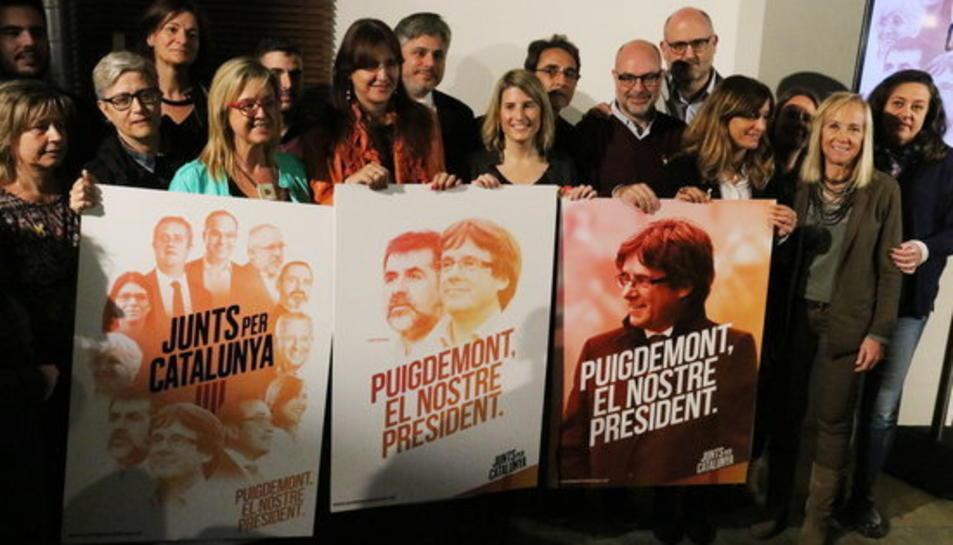 Els membres de la candidatura de Junts per Catalunya aguantant el tres cartells amb el lema de la campanya.