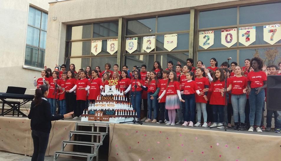 Imatge dels alumnes cantant una cançó commemorativa amb el pastís fet per l'AMPA de l'escola.