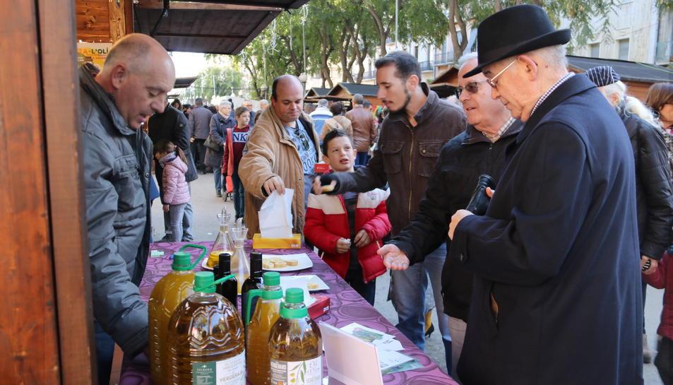 Pla mig d'una parada de la Fira de l'Oli DOP Siurana amb diversos clients tastant oli. Imatge del 3 de desembre de 2017