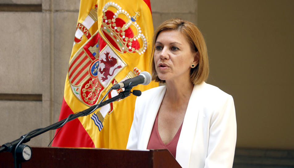 La ministra de Defensa, María Dolores de Cospedal, parlant amb una bandera espanyola darrere.