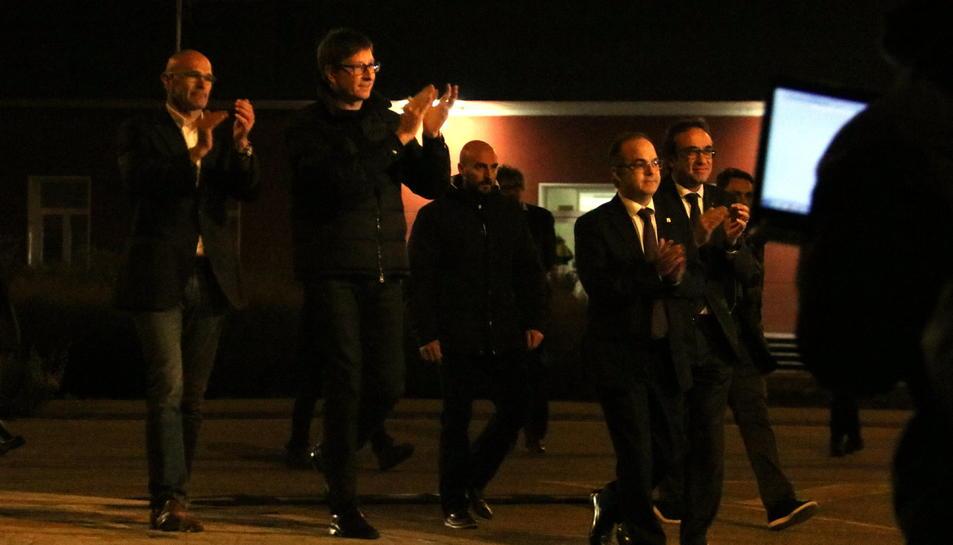 Romeva, Mundó, Rull i Turull amb les mans enlaire agraint el suport en el moment de sortir de la presó d'Estremera.