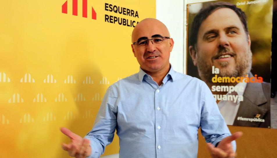 El cap de llista d'ERC per Tarragona, Òscar Peris, davant un cartell de campanya amb Oriol Junqueras.