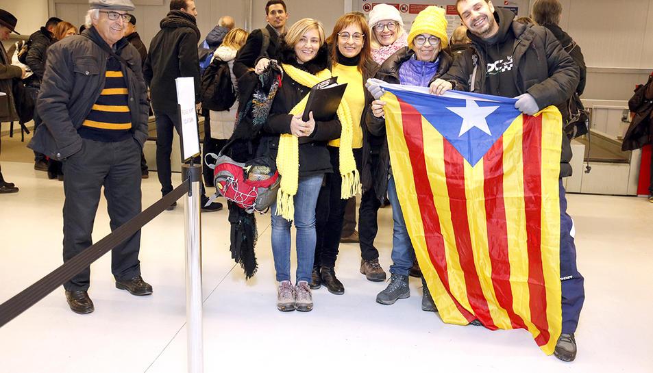 Un grup de gent amb una estelada fent cua per recollir la targeta d'embarcament a l'aeroport de Lleida-Alguaire per volar a Brussel·les.
