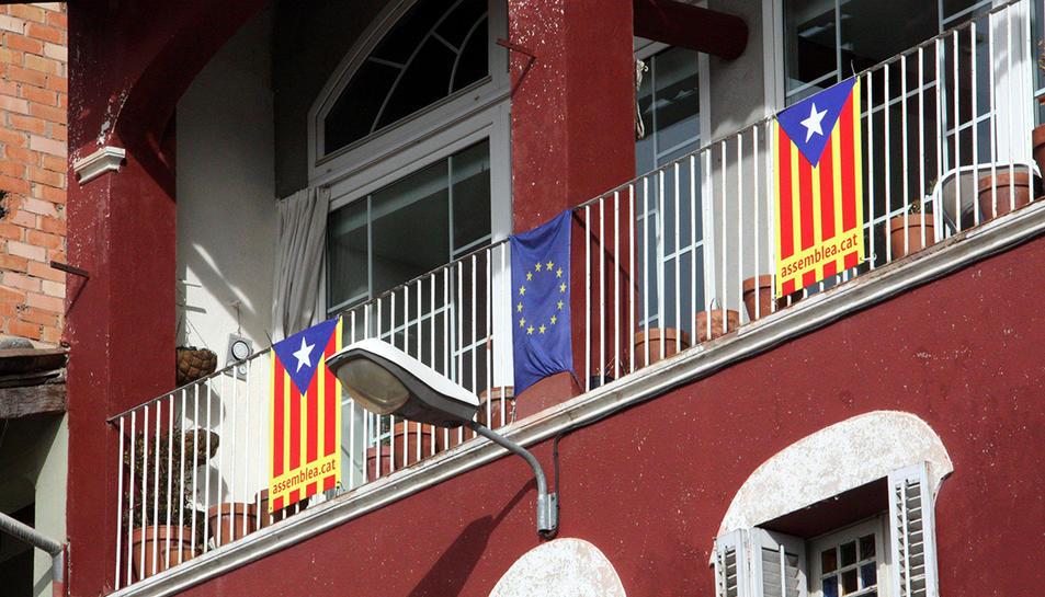 Banderes estelades en un balcó, al costat d'una bandera europea.