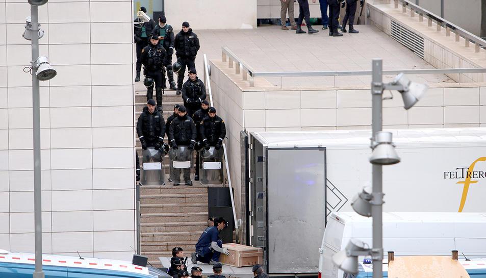 Un operari, protegit per un gran nombre d'agents de la Guàrdia Civil, carregant una de les obres al camió.