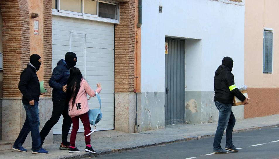 Agents dels Mossos s'emporten material i una detinguda d'una de les cases escorcollades al barri de les Quintanes d'Amposta.