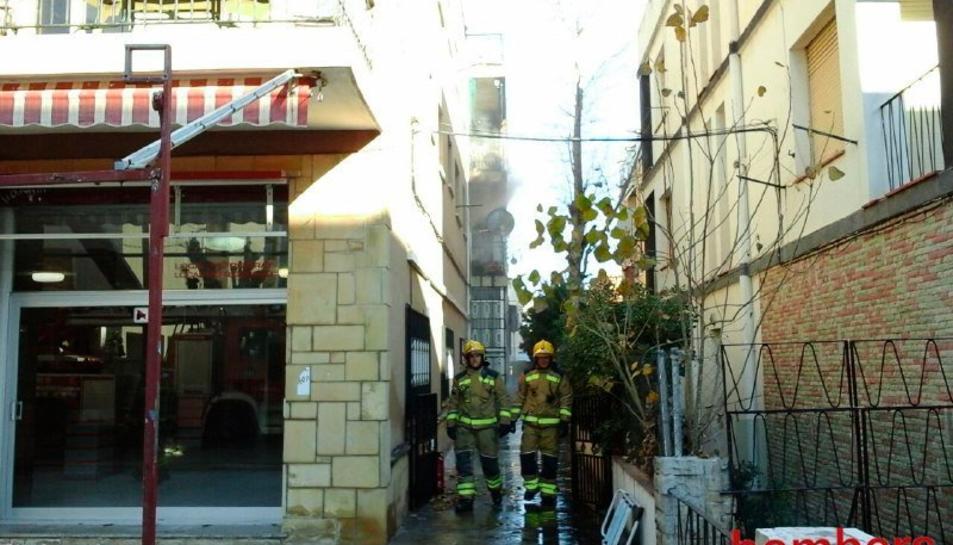 Imatge del pis de Calafell incendiat i dos dels bombers que han intervingut
