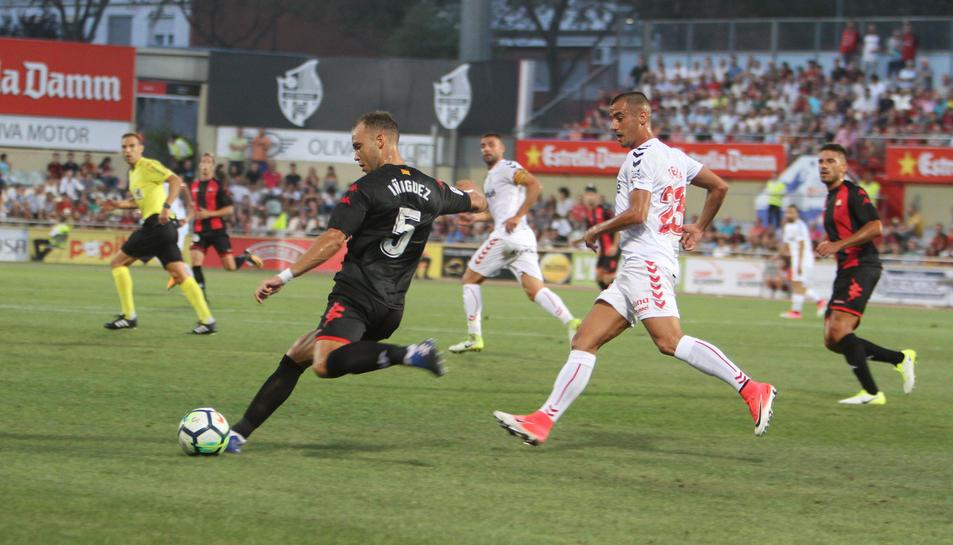 El central del CF Reus Pablo Íñiguez amb la pilota, al costat del grana Tejera.