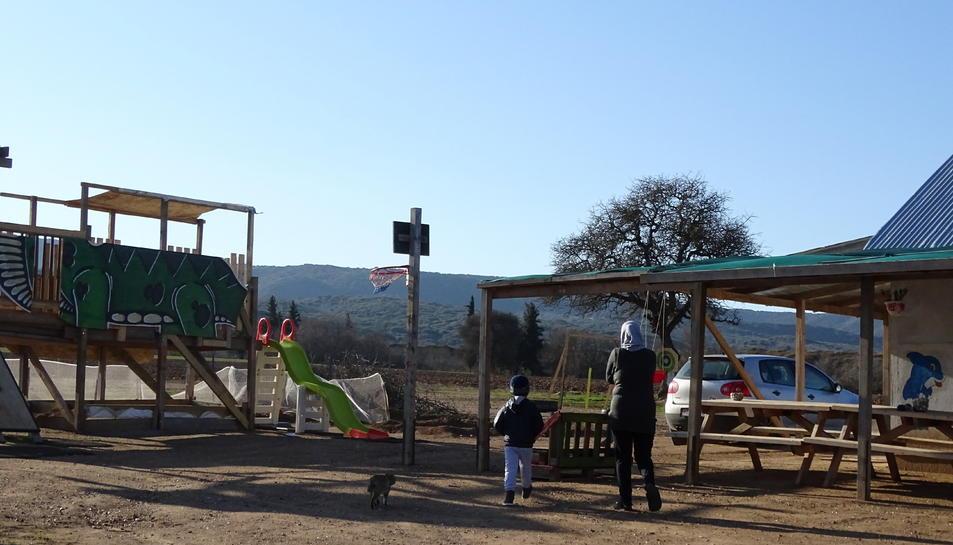 Una dona i un nen es dirigeixen a l'escola del camp.