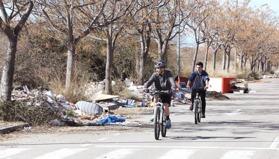 Dos veïns circulen en bicicleta per un dels carrers del polígon, completament envaït per les deixalles i la runa que s'ha abocat il·legalment.