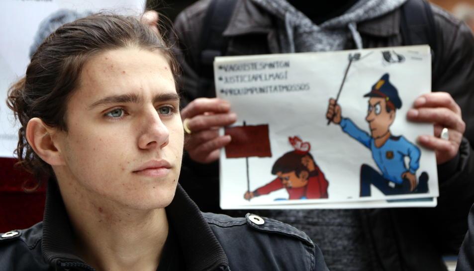 Primer pla de Magí Castro, el noi ferit per un cop de porra el 2012 a Tarragona, amb una vinyeta que recrea els fets al seu darrere. Imatge del 20 de febrer del 2018