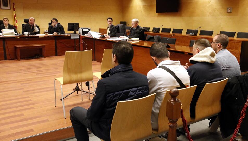 Els quatre acusats, entre els quals hi ha dos guàrdies civils, asseguts a la banqueta de la Secció Tercera de l'Audiència de Girona.