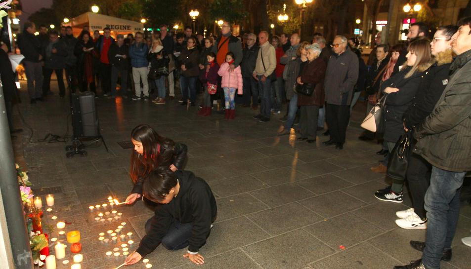Un nen i una nena encenen espelmes al lloc on la Carolina va morir el passat 9 de febrer.