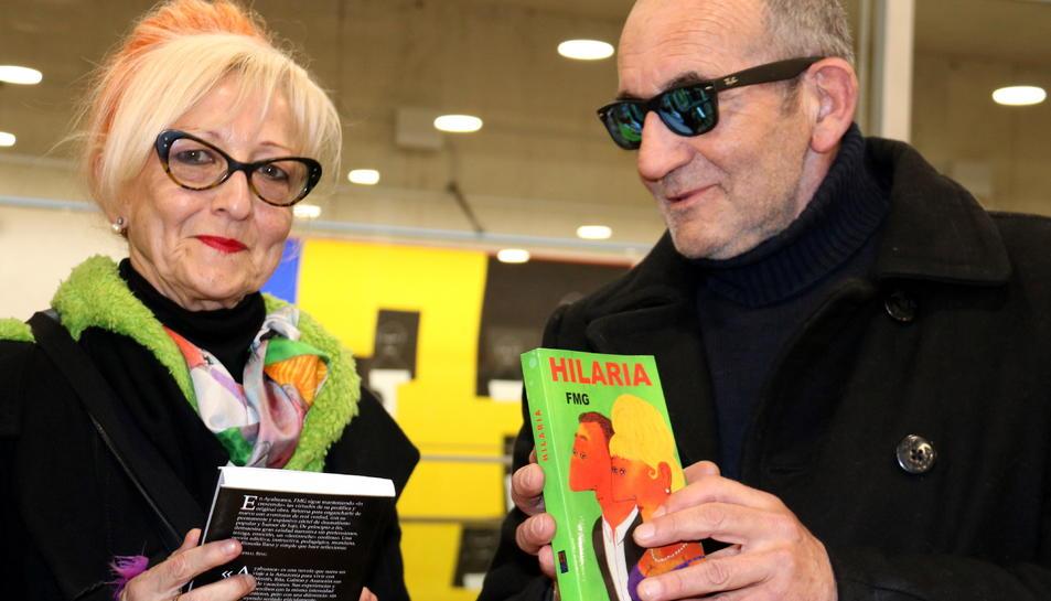 Pla mig de Elisabeth Sabala i Fernando Martínez García, a la Biblioteca Marcel·li Domingo de Tortosa, fullejant algunes de les novel·les de FMG il·lustrades amb pintures de tots dos. Imatge del 16 de febrer de 2018 (horitzontal)