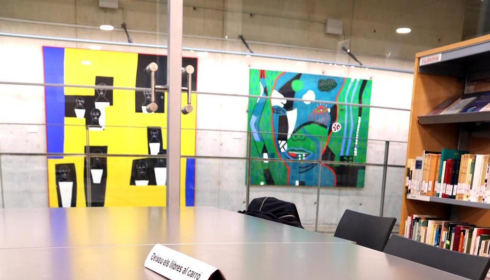Primera pla de dues novel·les de Fernando Martínez García sobre una taula de la Biblioteca Marcel·li Domingo de Tortosa amb els dos quadres que il·lustren la portada al fons exposats. Imatge del 16 de febrer de 2018 (vertical)