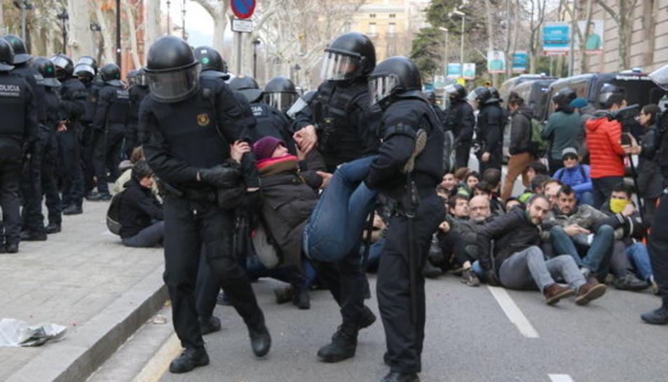 Un grup d'antiavalots dels Mossos d'Esquadra desallotgen una dona concentrada davant del TSJC.