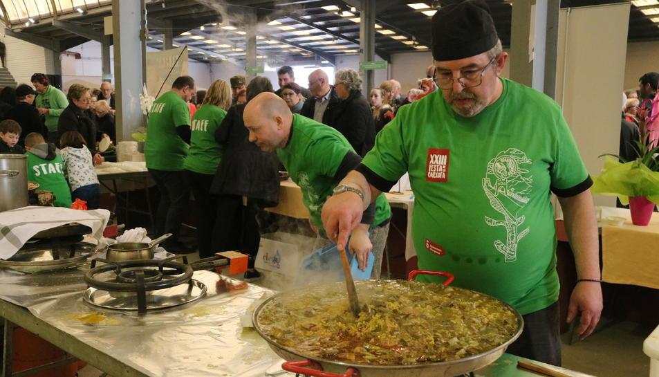 Pla mig d'un home cuinant arròs amb galeres i carxofa a la Festa de la Carxofa d'Amposta.