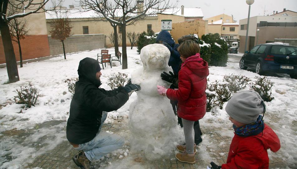 Infants fent un ninot de neu a l'Espluga de Francolí.