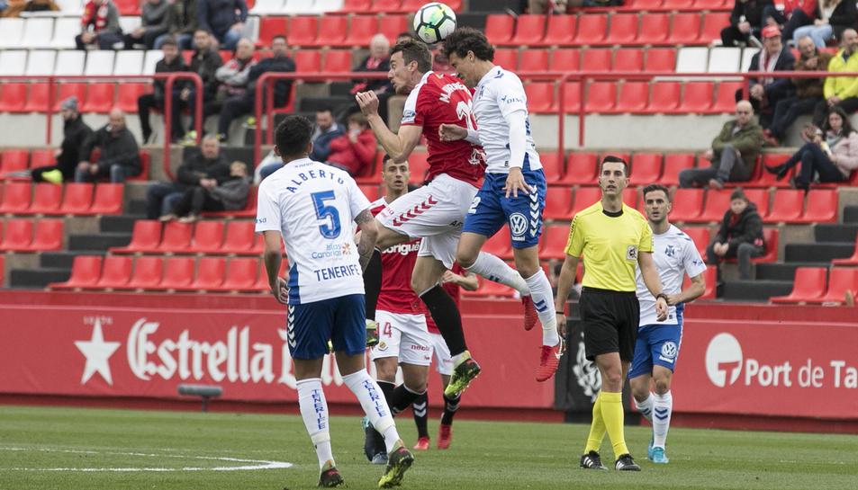 Manu Barreiro salta amb dos rivals durant el partit.
