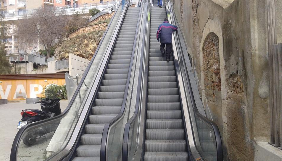 Dues persones pugen pel tram avariat, com si es tractés d'unes escales convencionals.